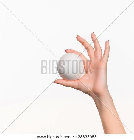 The female hand holding white blank styrofoam ball against the white background.