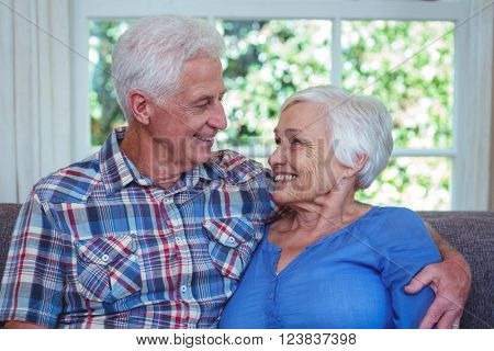 Happy senior couple looking at each other while sitting on sofa in living room