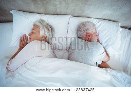 Overhead view of senior couple sleeping on bed