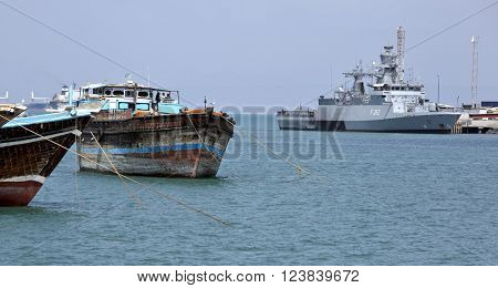 GULF OF ADEN, PORT OF DJIBOUTI - FEBRUARY 08, 2016: Traditional old style wooden fishing and cargo ships and EU WARSHIP F-262, German multipurpose corvette on background