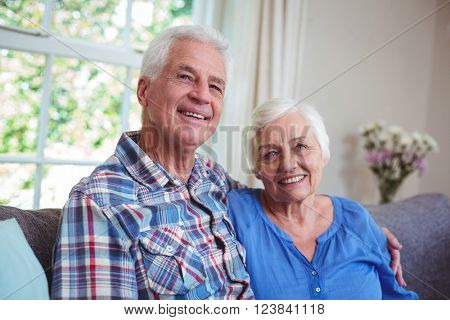 Portrait of happy senior couple sitting with arms around on sofa