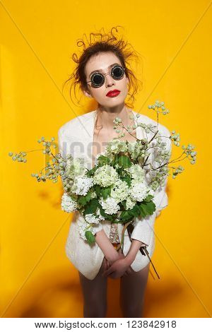 Beautiful fashion hipster in vogue sunglasses and flowers bouqet . model woman with professional make up and hairstyle on yellow background . photo