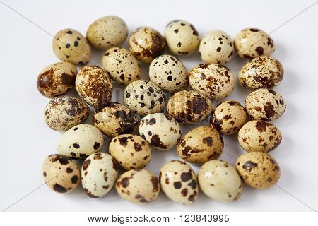 Several small yellow motley quail eggs lie on a white background. Small depth of sharpness. Focus in the center.