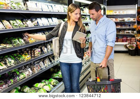 Cute couple choosing groceries together at the supermarket