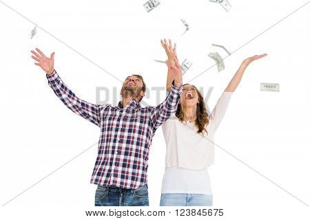 Happy young couple throwing currency notes in air on white background