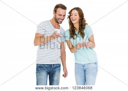 Happy young couple looking at mobile phone on white background
