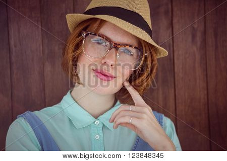 Ginger hipster with trilby and glasses on wooden background