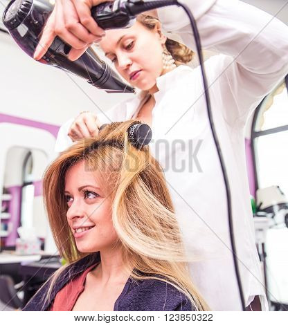 Hairdresser styling hair to her customer with blow dryer in a hair salon