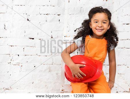 little girl in repairman uniform with helmet in hands
