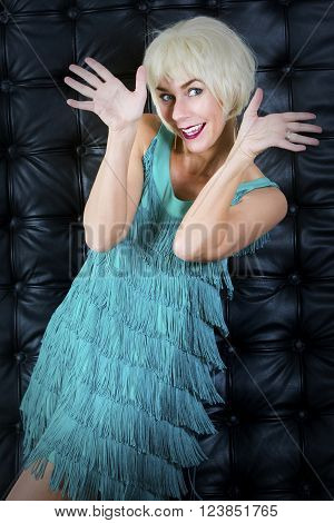 blond showgirl in green dress is dancing in front of black leather background