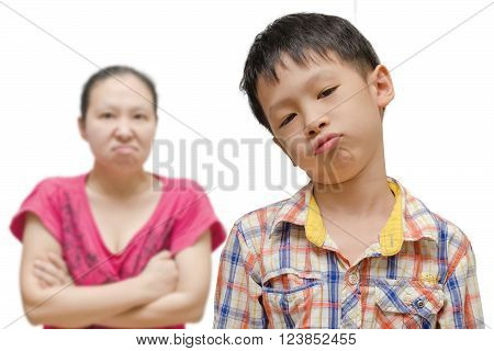 Unhappy boy with his angry mother in background
