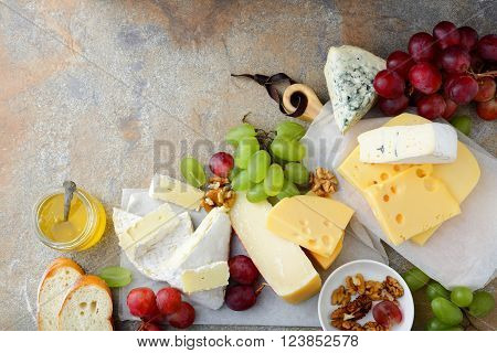 Various Types Of Cheeses With Grapes, Honey, Bread And Walnuts On The Slate