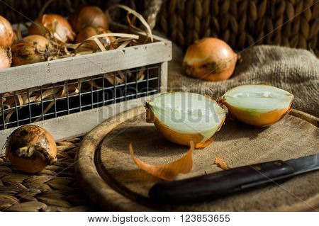 Onions on the rustic wooden cutting board. Chopped onions on rustic board. Onions in basket.