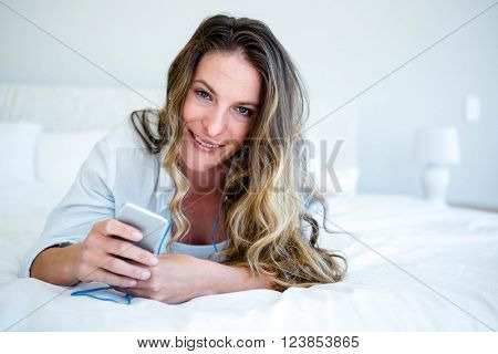 woman lying on her bed listening to music on her mp3 player