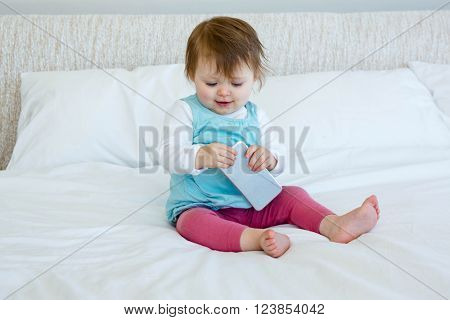 Smiling baby playing with a mobile phone on a bed
