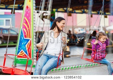 Cute little girl with her mother having fun at fun fair, chain swing ride, amusement park