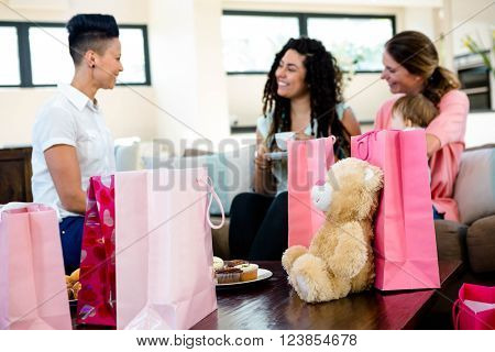 3 women and a baby sitting on a coch surrounded by gifts