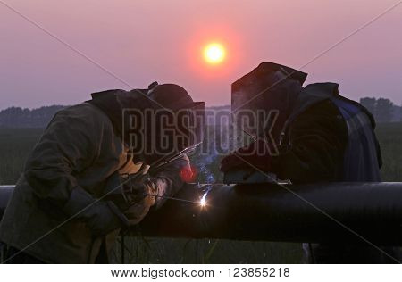 two welders working at sunset during a pipeline construction