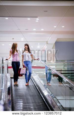 Two beautiful women carrying shopping bags on escalator of shopping mall