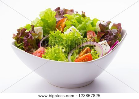 mixed vegetable salad with tomatoes onions and feta cheese in a white bowl on white background