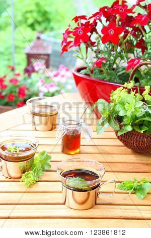 mugs from glass with honey on the garden table