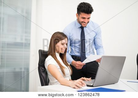 Business people using a laptop computer in their office. Focus on the woman