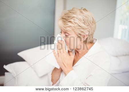 Senior woman covering nose with tissue while sneezing at home