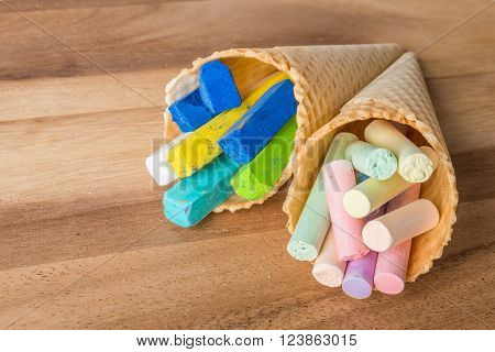 Close up of pastel chalks in wafer cones on wooden background