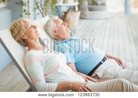 Senior couple relaxing on lounge chair at porch
