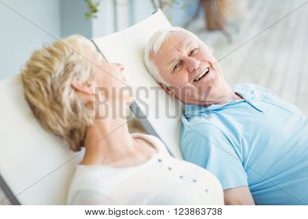 High angle view of happy senior couple relaxing on lounge chair at porch