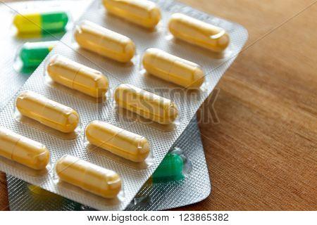 antibiotic capsule drugs in the packaging on wood background.