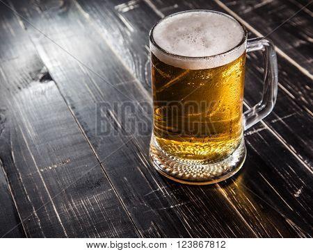 Mug of beer, on a black wooden background