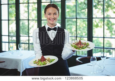 Smiling waitress holding plates in a restaurant