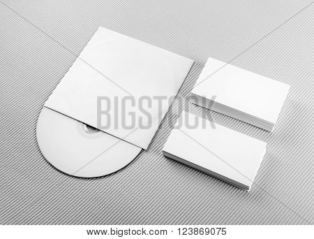 Blank business cards and CD on gray background. For design presentations and portfolios. Mockup for branding identity.