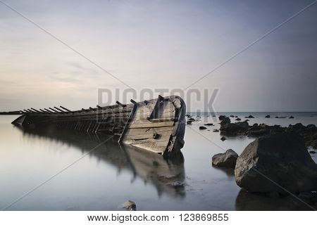 a shipwreck in shallow water and the sunset