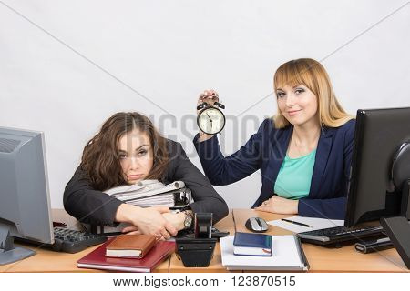 Two Girls In The Office At The End Of The Day, One With A Smile, Holding A Clock, Another Weary Lies