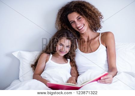 Portrait of mother and daughter reading book together on bed in bedroom