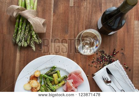 Green fresh and fried asparagus with ham potatoes and white wine.