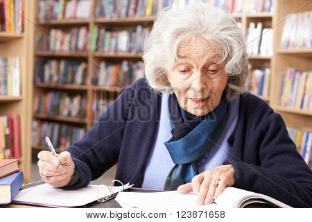 Senior Woman Working At Desk Studying In Library