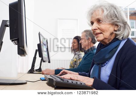 Senior Woman Attending Computer Training Class In Library