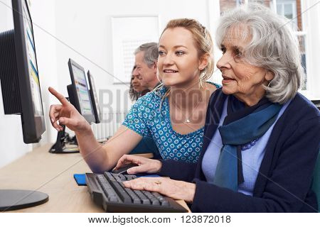 Tutor Helping Senior Woman In Computer Class