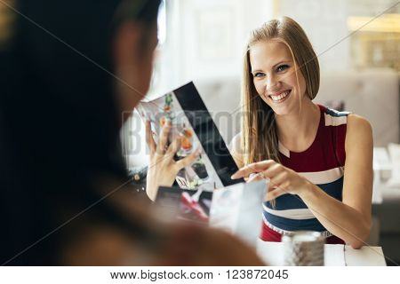 Beautiful women talking in restaurant before ordering a meal