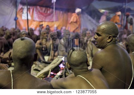 ALLAHABAD, UTTAR PRADESH, INDIA - FEBRUARY 06, 2013: Hindu Sannyasis (monks) and pilgrims at Maha Kumbh Mela festival gathered for joint praying. The world's largest religious gathering