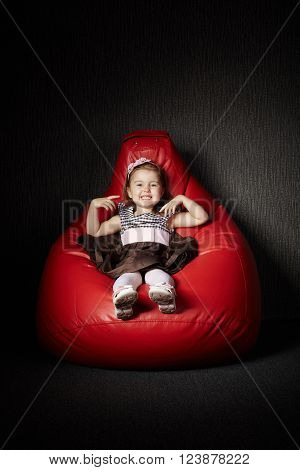 Little funny girl sitting on red beanbag