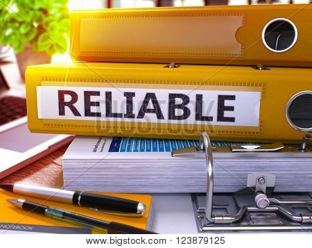 Yellow Ring Binder with Inscription Reliable on Background of Working Table with Office Supplies and Laptop. Reliable - Toned Illustration. Reliable Business Concept on Blurred Background. 3D Render.