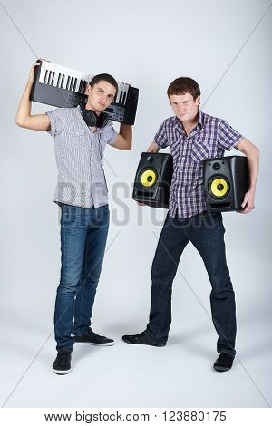 photo of two funny boys with speakers and piano