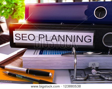 Black Ring Binder with Inscription SEO - Earch Engine Optimization - Planning on Blurred Background of Working Table with Office Supplies and Laptop. SEO Planning Business Concept. 3D Render.
