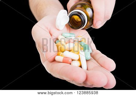 Pouring pills in hand from bottle as dosage or painkillers concept