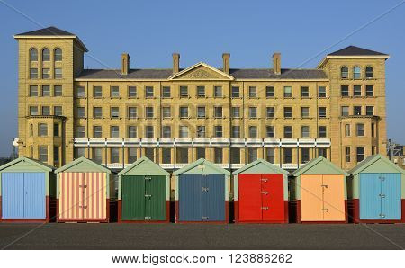 Multicoloured beach huts on seafront promenade at Brighton East Sussex England