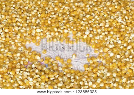 Geographical map of China covered by a background of corn seeds. This nation is the one of the five main producers and exporters of maize. Horizontal image.